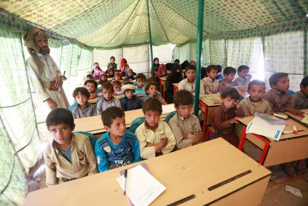 Displaced Yemeni students attend a class in a tent at a refugee camp located between Marib and Sanaa