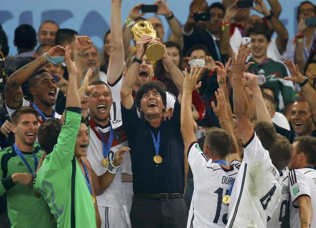 Germany's coach Loew lifts the World Cup trophy after his team won the 2014 World Cup final against Argentina in Rio de Janeiro