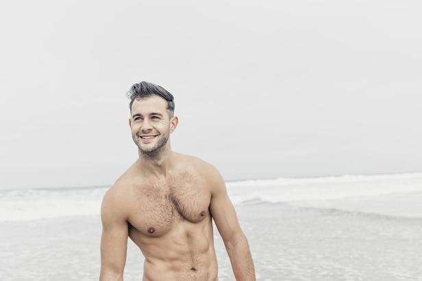 happy shirtless man at the beach.
