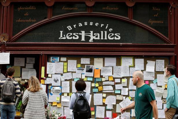 People look at tributes to chef and television personality  Anthony Bourdain outside Brasserie Les Halles in New York