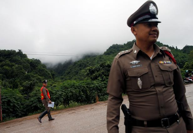Police officers walk near Tham Luang cave complex in the northern province of Chiang Rai