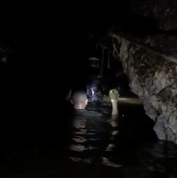 Rescuers wade in the flooded Tham Luang cave during a mission to evacuate the remaining members of a soccer team trapped in a flooded cave in Chiang Rai