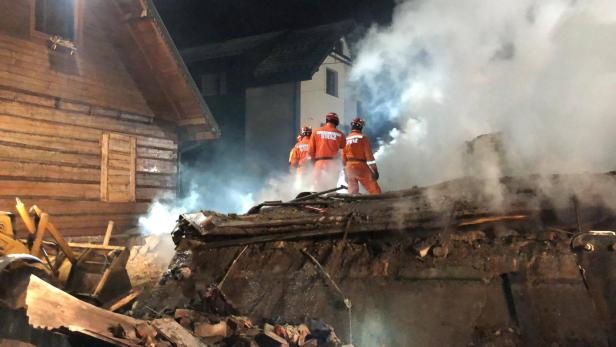 Firefighters work at the site of a building levelled by a gas explosion in Szczyrk