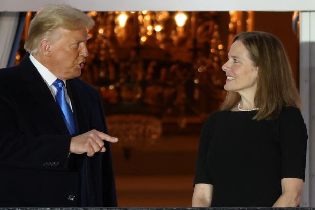 U.S. President Trump speaks with Judge Barrett after she was sworn into her seat on the U.S. Supreme Court on the South Lawn of the White House in Washington