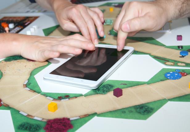 Autorenn-Brettspiel mit Tablet und drei Händen, die schnell drücken wollen