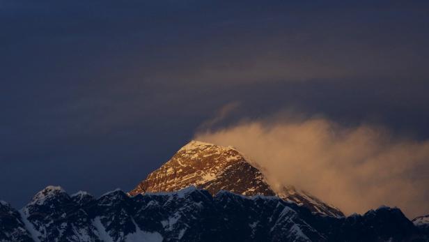 Light illuminates Mount Everest, during sunset in