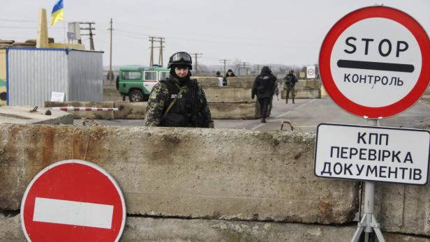 Ukrainian soldier is seen at a checkpoint at the r