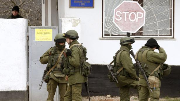 Armed men believed to be Russian servicemen stand