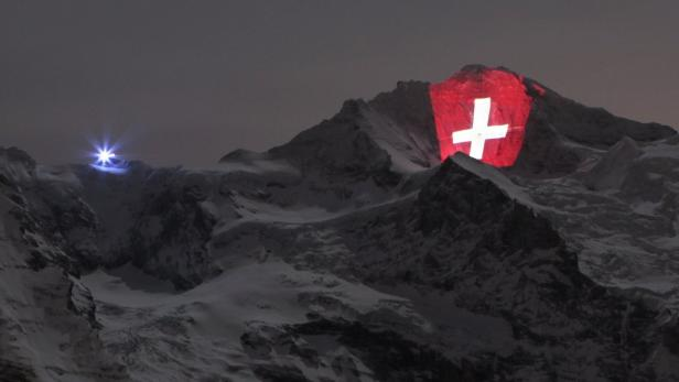 REUTERSA giant light installation of the flag of Switzerland, by Swiss artist Gerry Hofstetter, illuminates the north face of the Jungfrau mountain, in the Bernese Oberland January 1, 2012. The installation commemorates the 100-year anniversary of the Jun