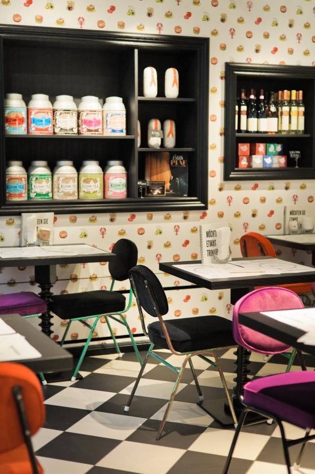 Das Bistro präsentiert sich mit bunten Grafik-Tapeten und Vintage-Stühlen.