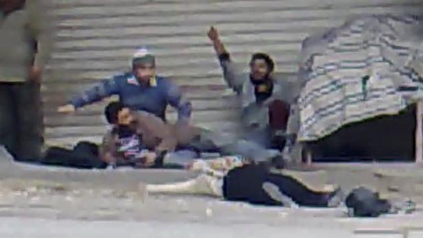 """Dieses Bild, am 15.12. von """"Ugarit News"""" über das Internet veröffentlicht, zeigt Männer, die den Körper einer Frau in Damaskus bergen wollen."""