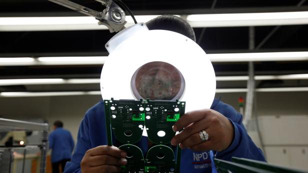 An employee inspects a printed circuit board at the assembly line of a factory that exports to the U.S. in Ciudad Juarez