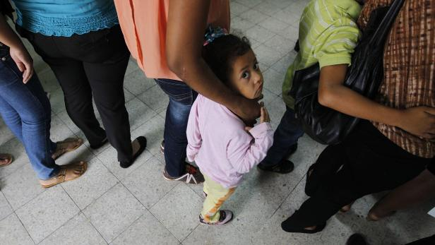 Women and their children wait in line to register at the Honduran Center for Returned Migrants after being deported from Mexico, in San Pedro Sula