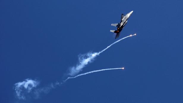 An Israeli air force F-15I fighter jet releases flares over the Mediterranean Sea during an aerial show as part of the celebrations for Israel's Independence Day marking the 70th anniversary of the creation of the state, in Tel Aviv