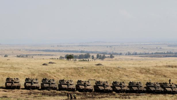 Israeli soldiers walk past tanks near the border with Syria in the Israeli-occupied Golan Heights