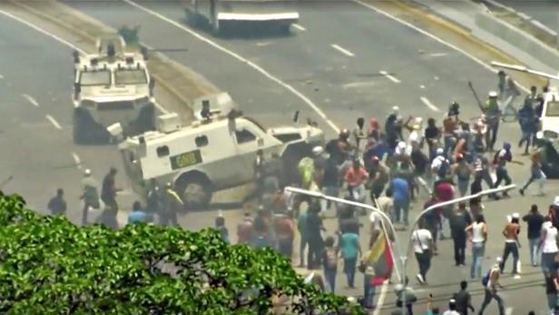 A Venezuelan National Guard vehicle ploughs into opposition demonstrators in Caracas