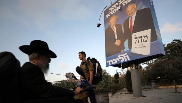 Ultra-Orthodox Jewish men walk past a Likud party election campaign banner depicting Israeli Prime Minister Benjamin Netanyahu and U.S. President Donald Trump in Jerusalem