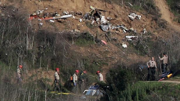 Sheriffs and officials investigate the helicopter crash site of NBA star Kobe Bryant in Calabasas, California
