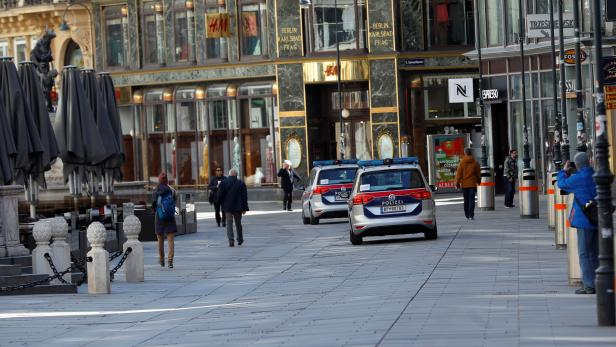 Police cars pass closed shops in Vienna
