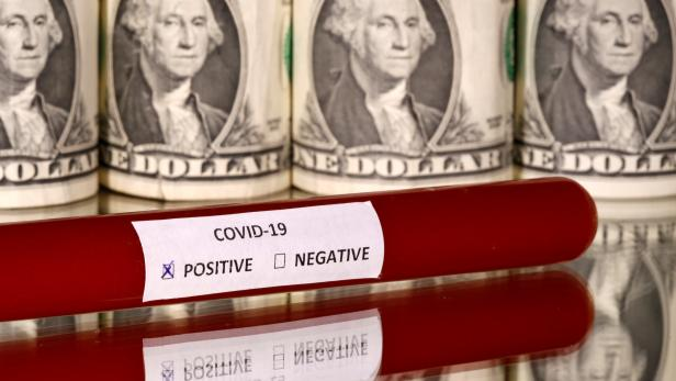 FILE PHOTO: Picture illustration of a test tube labelled with the coronavirus is seen in front of U.S. dollar banknotes