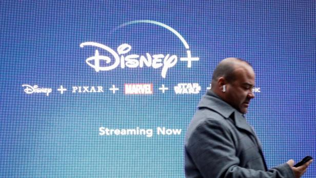 FILE PHOTO: A man looks at his phone as he passes by a screen advertising Walt Disney's streaming service Disney+ in New York, USA