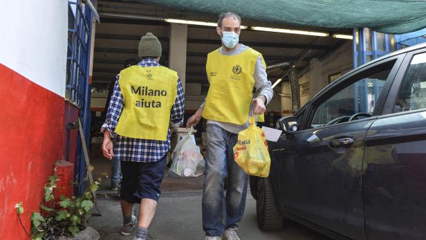 Volunteers deliver groceries and free food packages to families and people in need in Milan