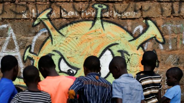 Children look at an advocacy graffiti by the Mathare Roots's youth group against the spread of the coronavirus disease (COVID-19), at the Mathare Valley slum, in Nairobi