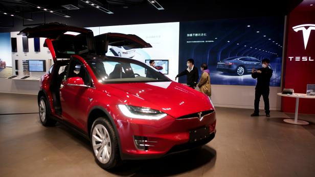 FILE PHOTO: People wearing face masks are seen inside a Tesla showroom at a shopping mall in Wuhan