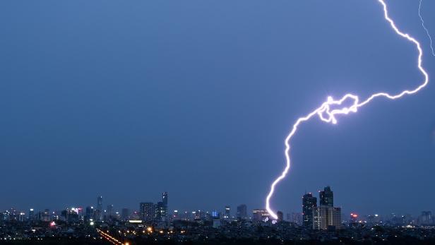 Ein Blitz schlägt über der Skyline von Hanoi ein.