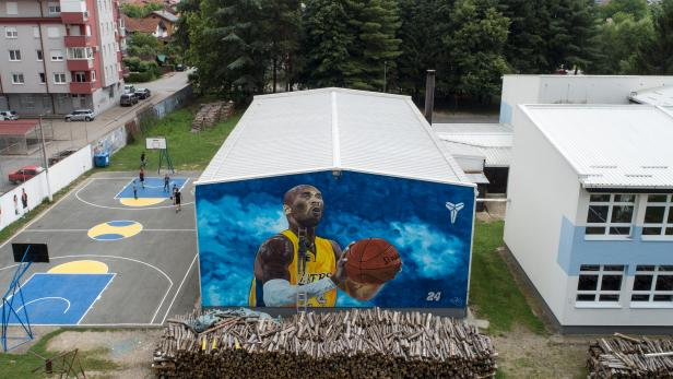 Artist Deni Bozic (27) paints the last details on his tribute mural honoring former Los Angeles Lakers basketball star Kobe Bryant on a school building wall in Gradiska