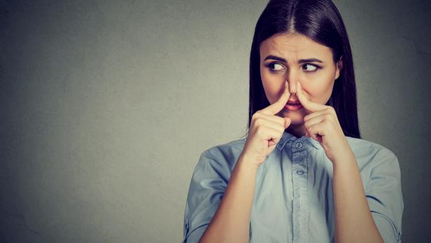 Woman pinches nose with fingers looks with disgust away something stinks bad smell