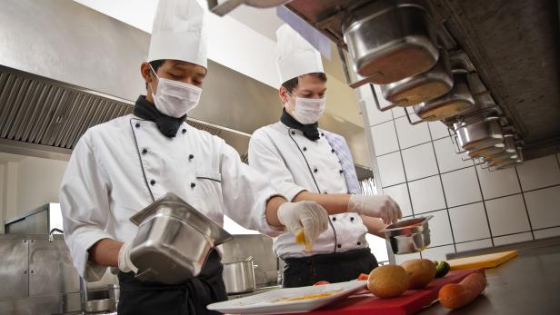 Chef and trainee work in a hotel kitchen, preparing a meal