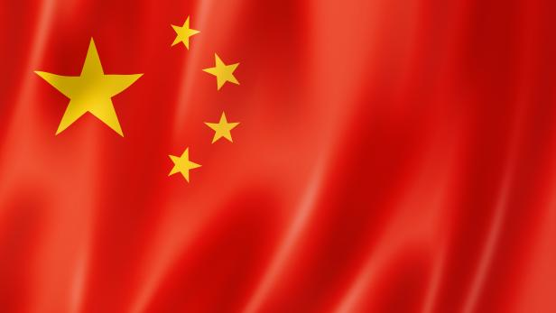 An up close image of a chinese flag with waves
