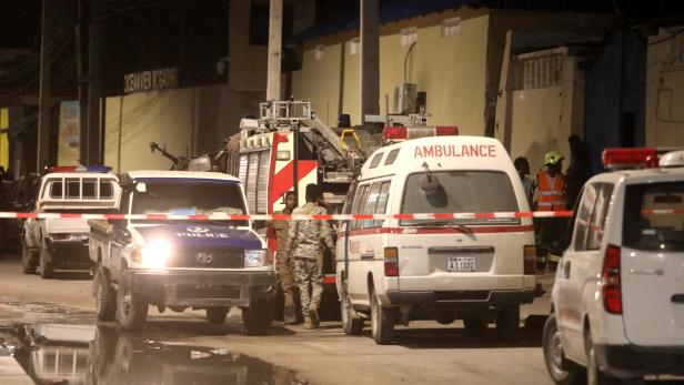 Emergency vehicles are seen at a cordoned off area near the site of a blast at the Elite Hotel in Lido beach in Mogadishu