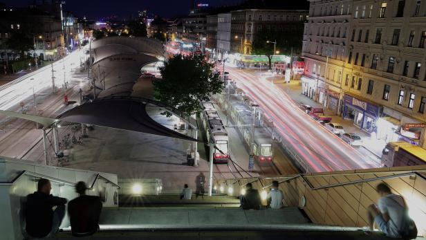 People sit on steps above the main library while traffic is seen on Guertel road in Vienna