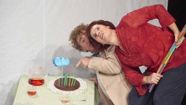 Zwei Schauspieler_innen vor der Torte am schrägen Tisch