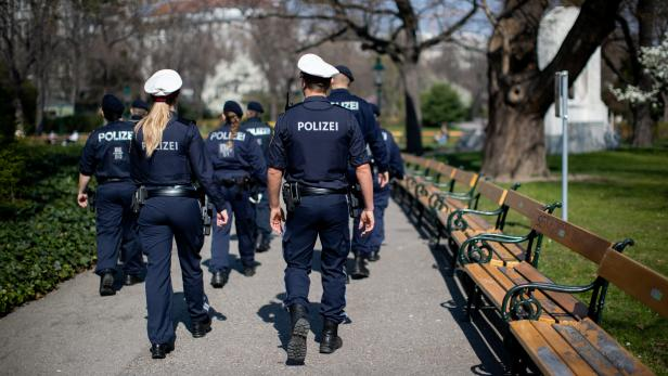 Police officers patrol Stadtpark as park benches are empty on a sunny spring day during the coronavirus disease (COVID-19) outbreak in Vienna