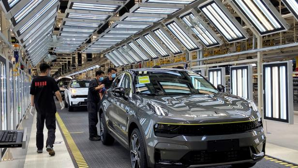 FILE PHOTO: Employees wearing face masks work on a Lynk &Co car production line at Geely's Yuyao plant in Ningbo