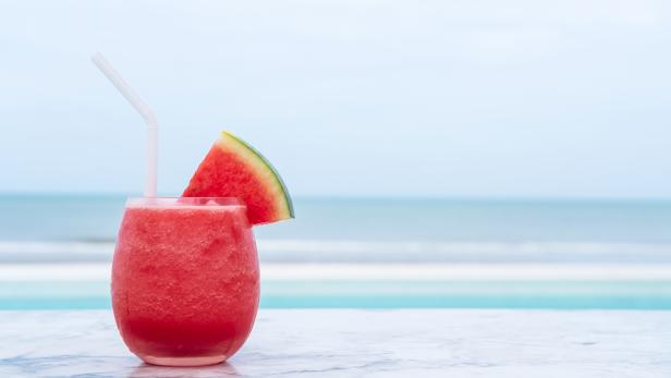 Watermelon smoothie on blue tropical beach. Summer holiday concept.