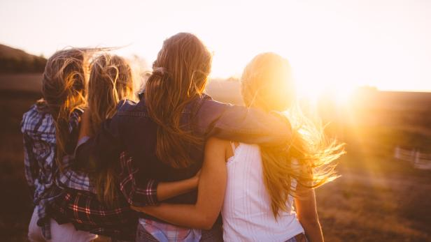 Teen girls facing the sunset with on a summer evening