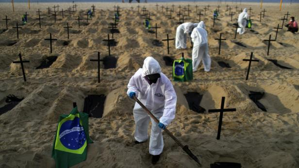 FILE PHOTO: Activists of the NGO Rio de Paz in protective gear dig graves on Copacabana beach to symbolise the dead from the coronavirus disease (COVID-19) during a demonstration in Rio de Janeiro