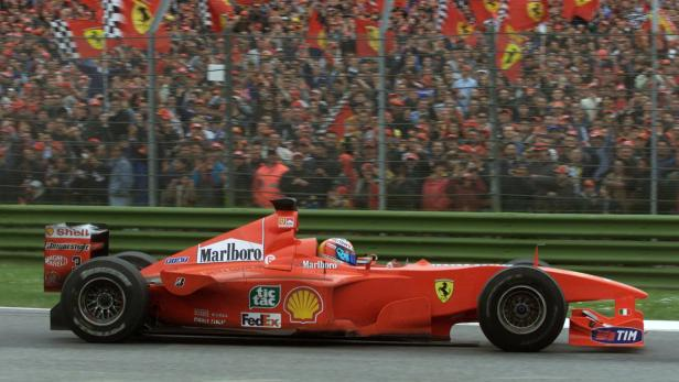 FILE PHOTO: Germany's Michael Schumacher drives past Ferrari fans en route to a narrow victory over Mika Hakkinen in the San Marino Grand Prix.