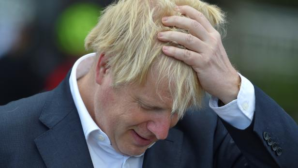 Britain's Prime Minister Boris Johnson reacts as he speaks to local cyclists at the Canal Side Heritage Centre in Beeston