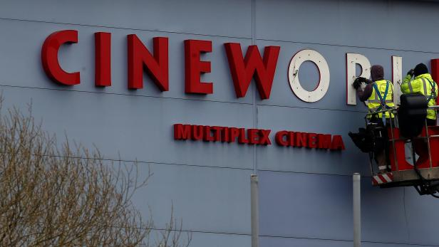 FILE PHOTO: Workers repair a sign at a Cineworld cinema in Bradford northern England.