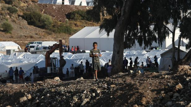 A boy carries a bottle of water in a temporary camp for refugees and migrants on the island of Lesbos