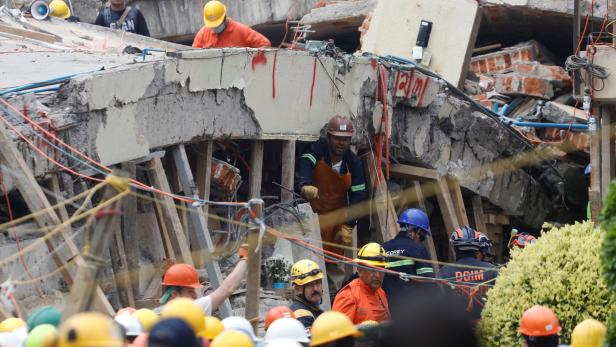 Rescue workers search through the rubble for students at Enrique Rebsamen school after an earthquake in Mexico City