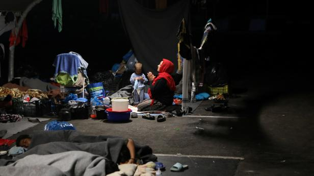 A woman prays as refugees and migrants from the destroyed Moria camp find shelter at the parking space of a supermarket, near a new temporary camp on the island of Lesbos