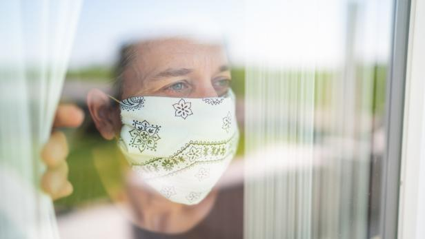 mature adult woman with mouse nose mask looking out through the window