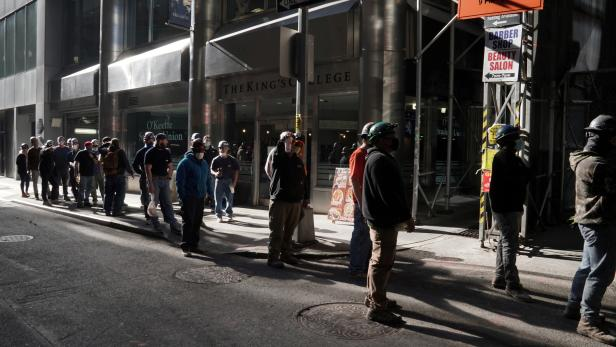 Construction workers wait in line to do a temperature test to return to the job site