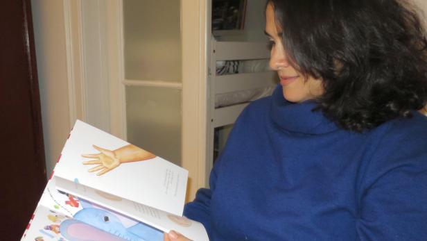 Autorin blättert ihr Bilderbuch fürs Foto durch